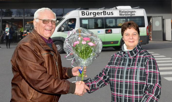 Udo Heggemann vom BürgerBus-Verein 3 Rosen überreicht dem 5000-sten Fahrgast zum Dank einen Blumenstrauß. Bild: Gerhard Müller