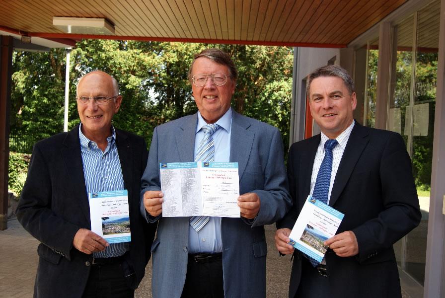 Bruno Maier, Egon Graf und Bürgermeister Ralf Baumert präsentieren den Geschenkscheck vor dem Rathaus.