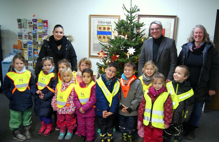 Freuen sich über die Adventsstimmung im Rathaus - Bürgermeister Ralf Baumert mit den Kindern und deren Erzieherinnen Melanie Messmer (links) und Stefanie Mensak aus dem Kinderhaus St. Raphael.