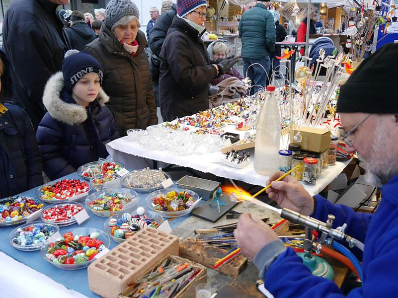 Viele Zuschauer bewundern beim Rielasinger Weihnachtsmarkt den Glasbläser Detlef Greiner-Perth bei der Arbeit. Bild: Ingeborg Meier