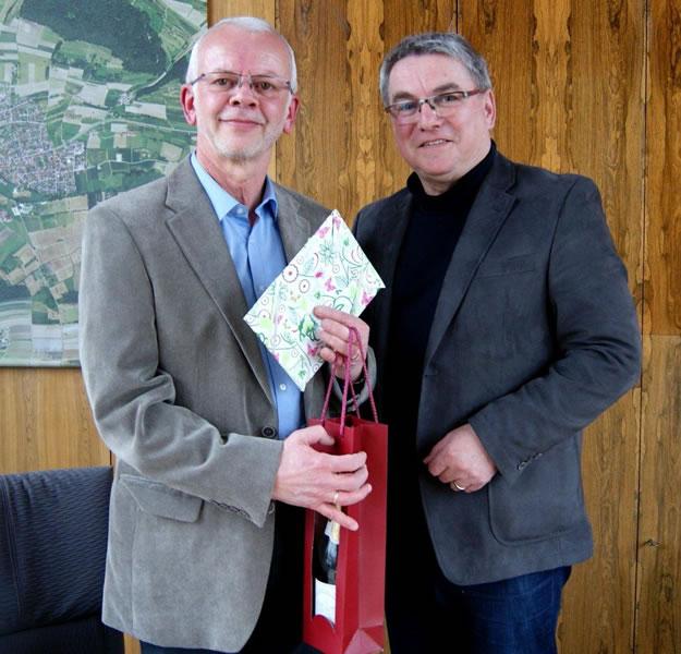Mitarbeiter Bernhard Weißer freut sich über die Glückwünsche und Präsente von Bürgermeister Ralf Baumert zu seinem besonderem Dienstjubiläum.