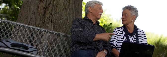 Zwei Senioren mit Notebook auf einer Bank im Grünen.