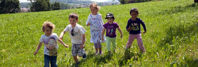 Fünf spielende Kinder auf einer Wiese.