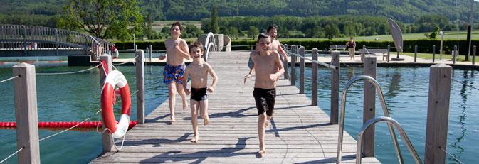 Kinder rennen über die Brücke im Naturbad Aachtal.