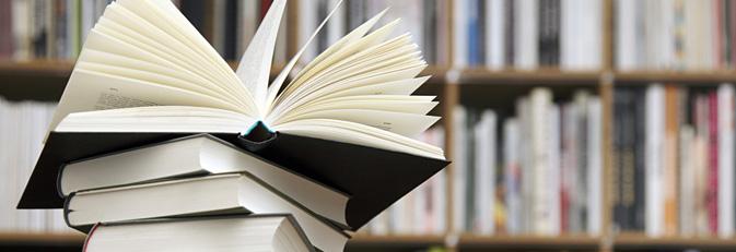 Bücherstapel vor einem Bücherregal.