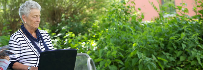 Zwei Senioren mit Laptop auf einer Bank im Grünen.
