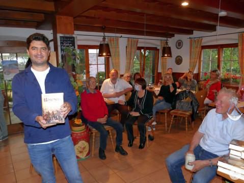 Herr Klemann präsentiert stolz sein Debütroman vor dem begeisterten Publikum. Bild: Sandra Bossenmaier