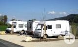 3 Wohnmobile am schön gelegenen Stellplatz beim Naurbad Aachtal mit der Aach im Vordergrund.