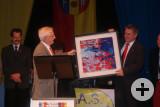 Bürgermeister Ancelin übergibt Bürgermeister Baumert ein Gemälde als Geschenk.