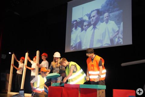 Auf der Leinwand im Hintergrund Originalbilder vom Beginn der Bauarbeiten der Ten-Brink-Schule. Auf der Bühne stellen die Schüler dies nach.