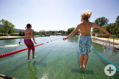 Zwei Kinder springen ins Schwimmerbecken des Naturbades Aachtal.
