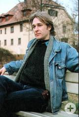Louis Perrin sitzend auf einer Bank. Im Hintergrund die Alte Mühle.