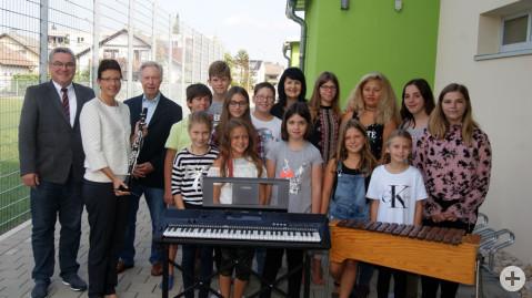 Musikschuldirektorin Ulrike Brachat und ihre Gesangsschüler freuen sich über neue Instrumente für die Musikschule.
