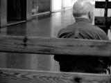 Älterer Mann wartend auf einer Bank.