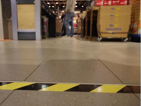 """Die """"sozial distance"""" im Zuge der Corona-Pandemie wurde auch im Edeka Markt Münchow in Rielasingen mit Klebebändern deutlich markiert. swb-Bild: of"""